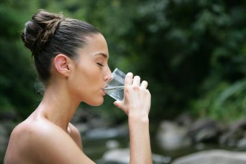Portrait of young woman drinking water from a glass