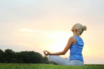 Young beautiful woman practicing yoga while sitting on grass